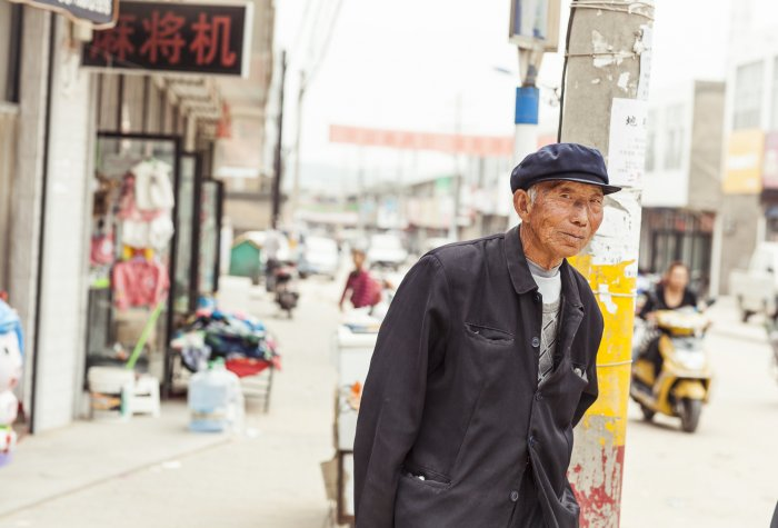 Old man on urban street in China.