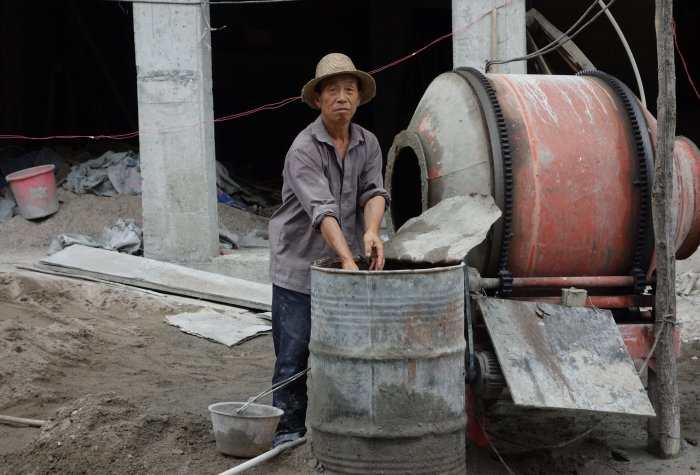 Man mixies cement in a construction site in China.