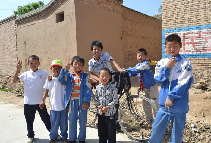A group of school boys in school uniforms pose in a rural village in China.