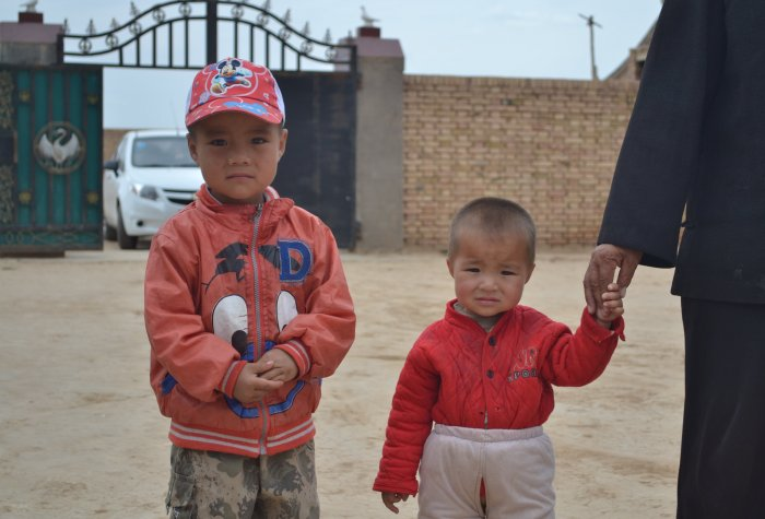 Two young boys stand in a driveway in rural China.