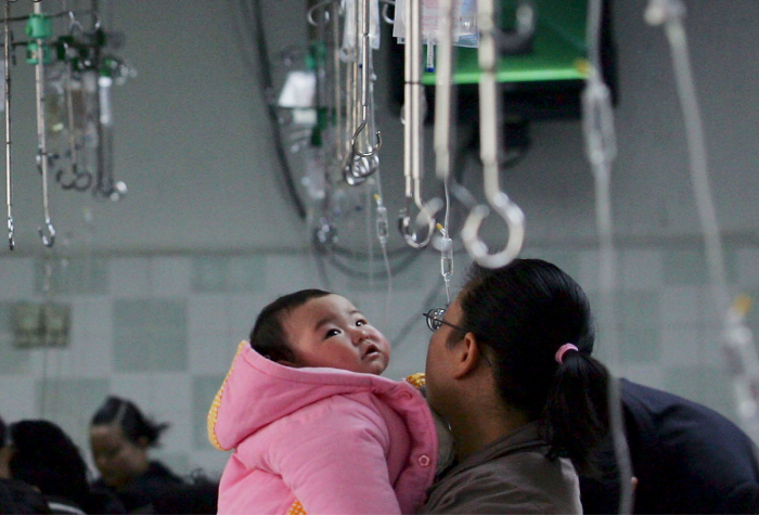 A parent holds a child waiting to be given an infusion at an area hospital in China.