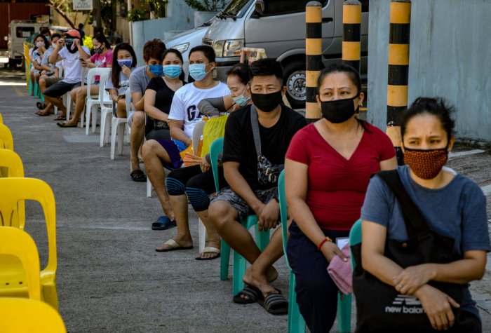People queue while wearing face masks