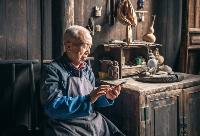 Chinese senior man tapping on mobile phone in wooden house.