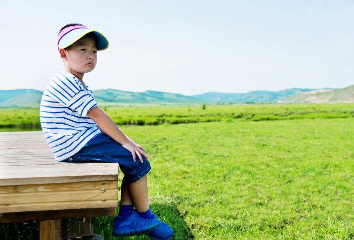 A boy sits alone on a wood deck over a green field in China.
