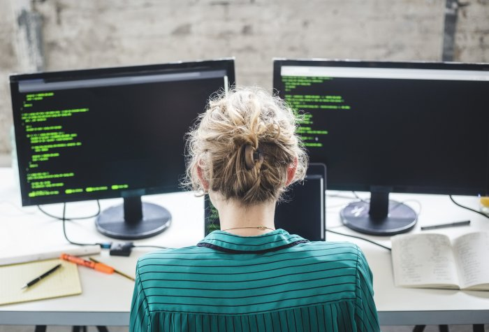 Female computer coder looking at a dual monitor with code on it.