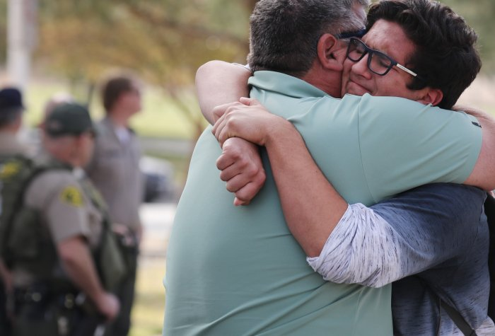 A boy hugs his father after a school shooting in Santa Clarita, CA.