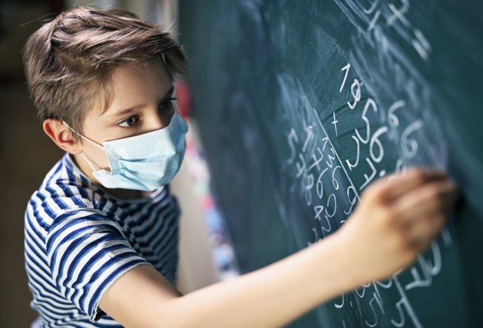 Boy in mask at chalkboard