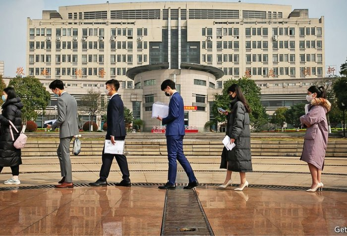 Young Chinese students stand in line in front of a large building in China.