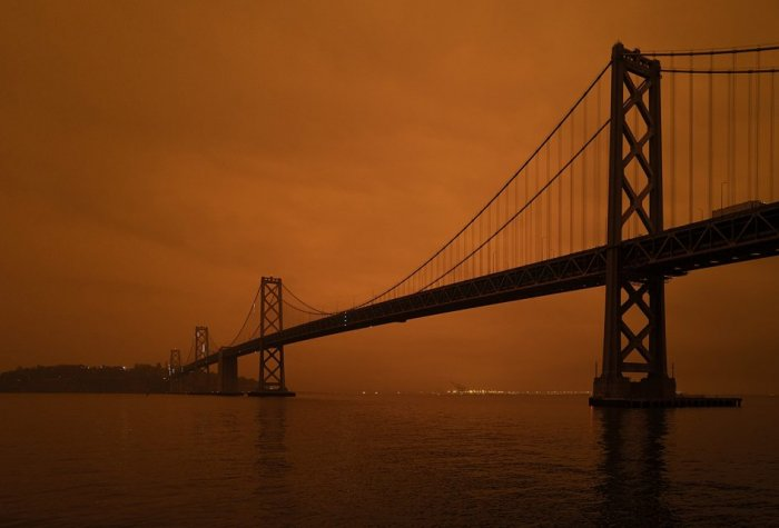 An orange smokey sky behind a dark bridge over water