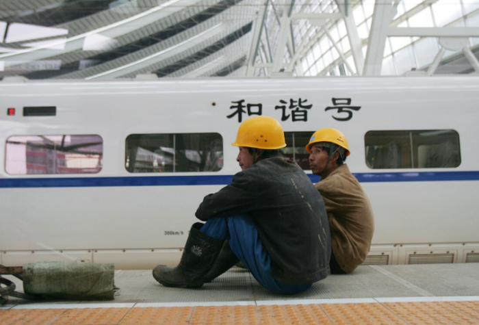 "BEIJING, CHINA - Workers sit near a CRH (China Railway High-speed) ""bullet train"" at the Beijing South Railway Station under reconstruction."