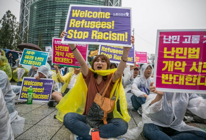 Demonstrators in South Korea sitting on the ground and carrying signs in Korean