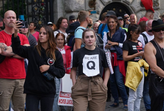 Mostly right-wing protesters, including a young woman wearing a QAnon shirt, in Berlin