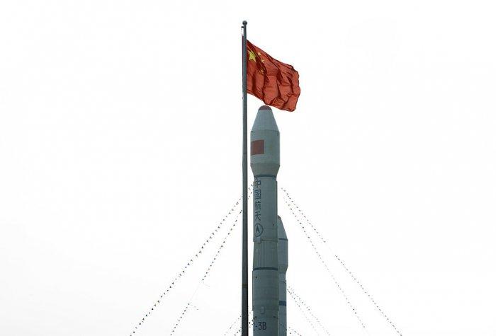 Chinese flag flying above orbital carrier rocket