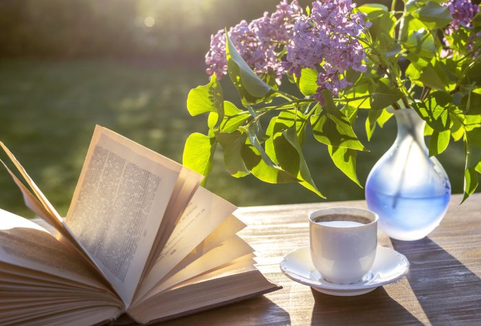 Little white cup of espresso coffee, opened book, blue semi-transparent vase with purple lilac flowers on rustic wooden table in the garden at spring morning after sunrise or at evening before sunset