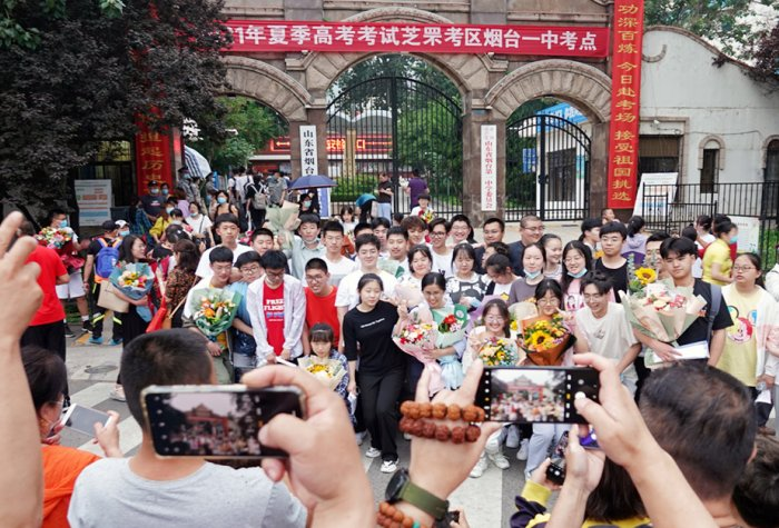 Crowd takes photos on their smartphones of a group of graduates in front of a Chinese university.