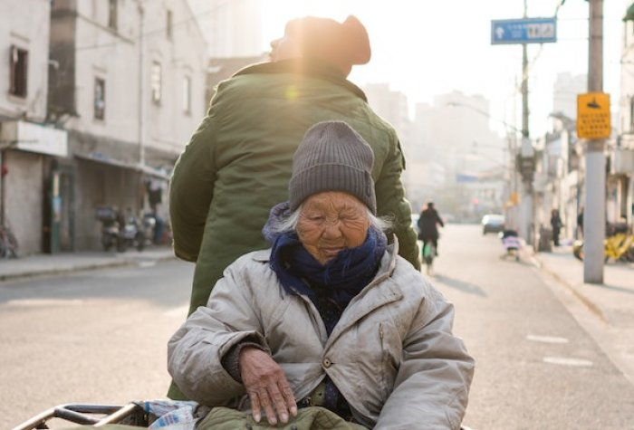 An elderly individual travels in a cart up a street.