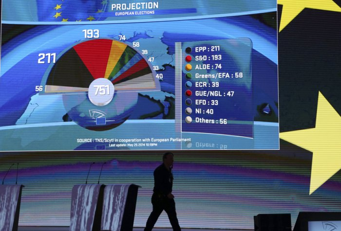 A man walks past a board displaying provisional results of the European Parliament election at the EU Parliament in Brussels