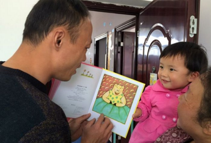Li, who used to enforce China's one child policy, works with REAP to become an early childhood development expert. Here, he reads a book to a child in an impoverished area of Danfeng County.