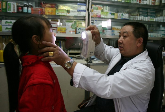 A doctor checks a young girl in a countryside clinic at Shihao Township on October 13, 2007 in Qijiang County of Chongqing Municipality, China.