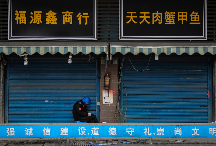 A security guard sits outside a closed market in Wuhan, China.