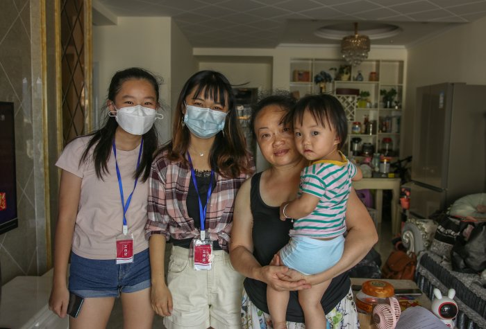 Researchers wearing masks visit caregivers and their children for the qualitative interviews and pose for a picture.