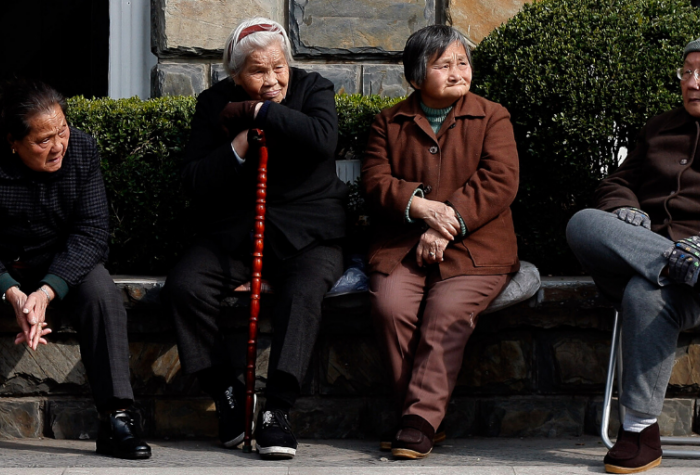 Elderly Chinese citizens sit together on a park bench.