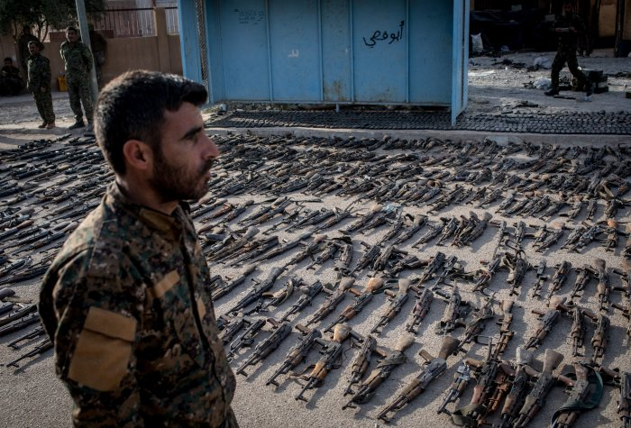 An SDF (Syrian Democratic Forces) fighter looks over seized ISIL weapons