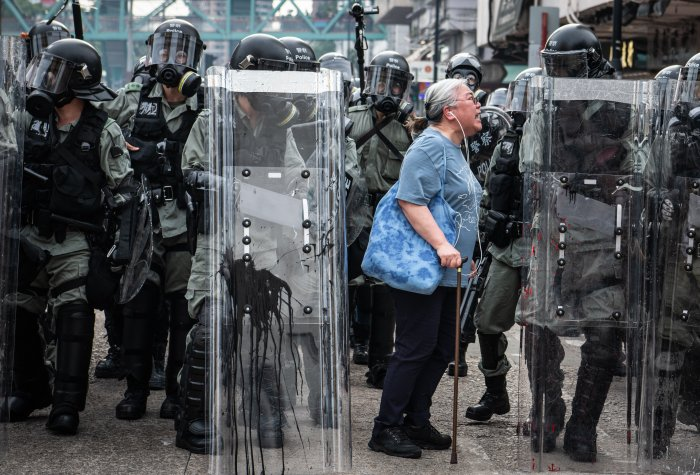 Woman shouts at police officers as they advance towards protesters in Hong Kong
