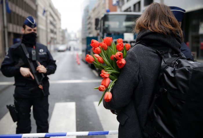 A woman arrives with flowers at a cordoned-off area near Maelbeek subway station in Brussels on March 23, 2016, a day after bomb attacks in the Belgian capital killed about 35 people and left more than 200 people wounded.