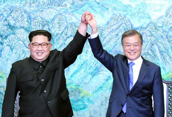 North Korean leader Kim Jong Un (L) and South Korean President Moon Jae-in (R) pose for photographs