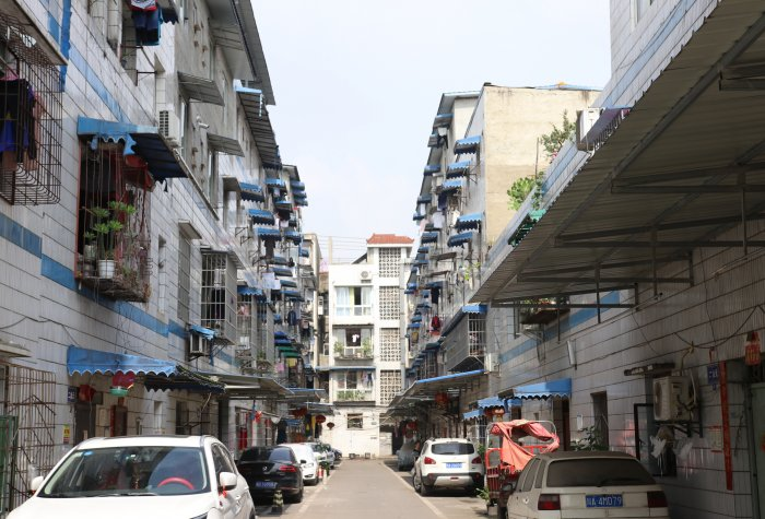 City street in Chengdu lined with older multi-story apartment buildings.