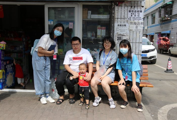 REAP researchers pose with caregiver and child outside of their family-run store.