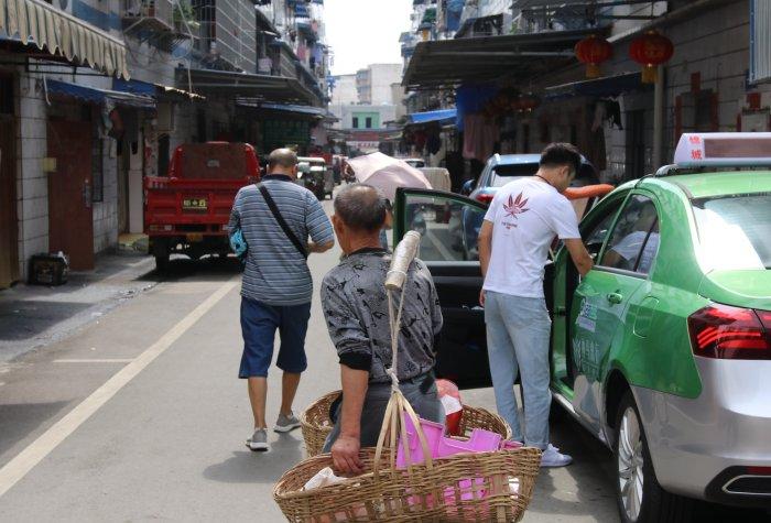 Elderly man carrying a heavy basket of food through a busy street in Chengdu.