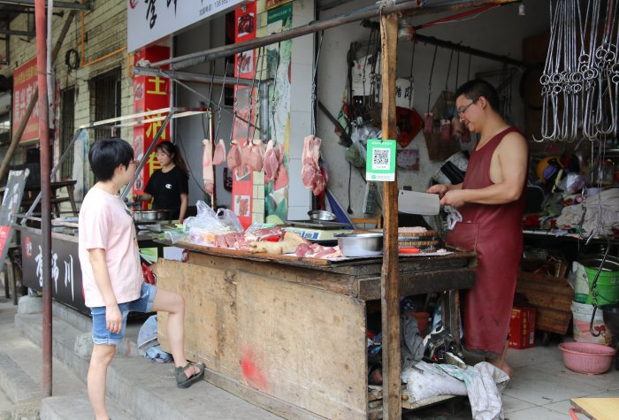 Woman waits for her meat from a road-side Chengdu butcher.