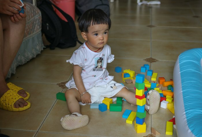 Child sits with building block toys on the living room floor.