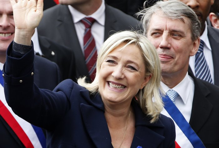 Image of Marine Le Pen (front) waving at supporters during gthe National Front's annual May Day rally in Paris May 1, 2014