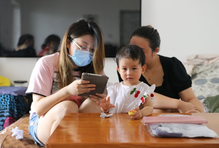 Caregiver looks at REAP's survey form as her child plays with a rubber duck toy.