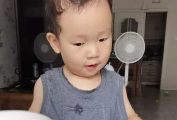 Toddler wearing a LENA vest with the LENA recording device in the front pocket.