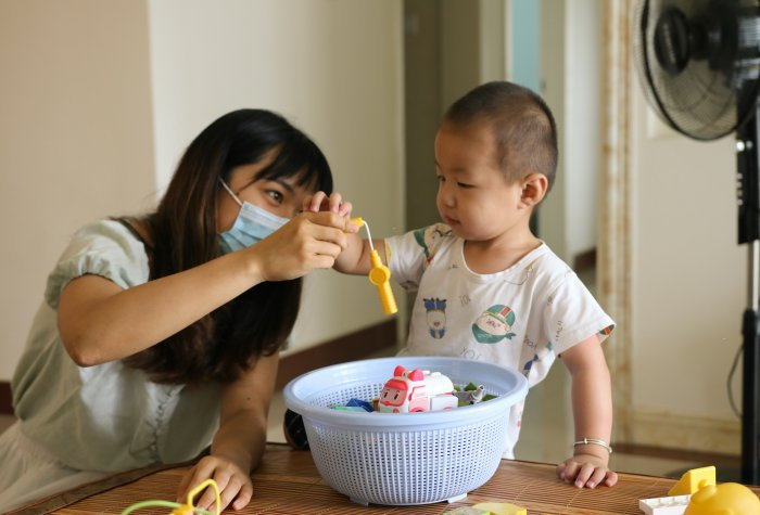 Researcher wearing a mask plays with a child and her basket of toys.
