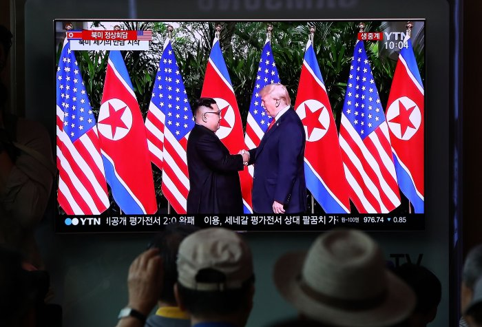 South Koreans watch on a screen reporting on the U.S. President Trump meeting with North Korean leader Kim Jong-un at the Seoul Railway Station on June 12, 2018 in Seoul, South Korea