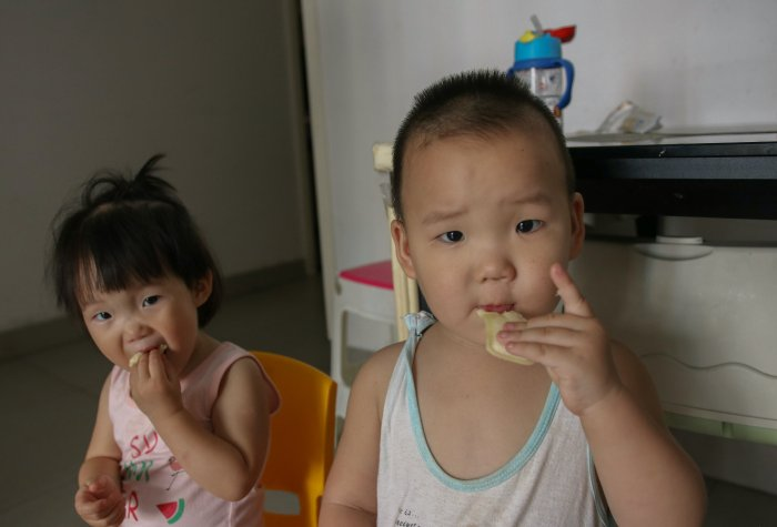 A pair of young twins share an afternoon snack in their living room.