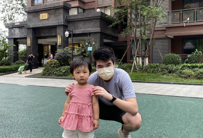 Tyler, a REAP intern on the survey team, poses with a migrant child at a playground in her recently-renovated apartment compound.