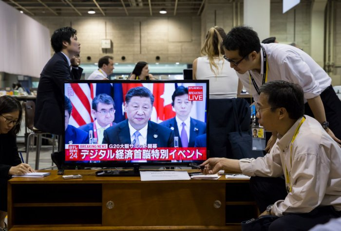 Journalists watch a live broadcast of China's President Xi Jinping speaking during the first session of the G20 summit on June 28, 2019 in Osaka, Japan.
