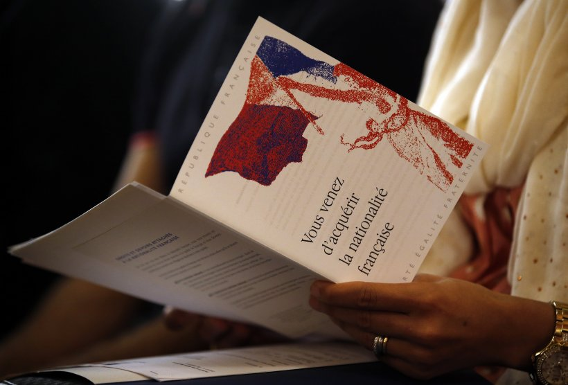 Image of a woman holding her French naturalization decree.