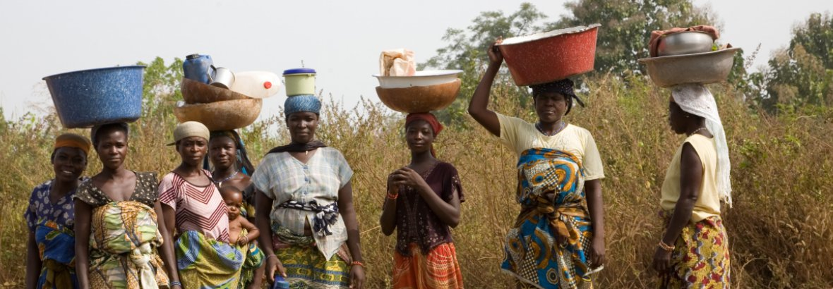 Smallholder farmers walk to collect water in Benin