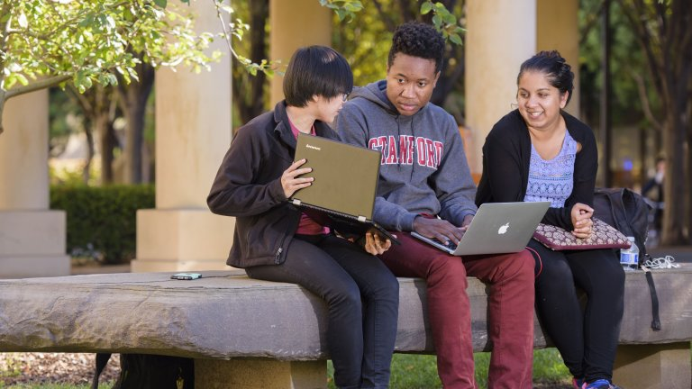 Three students conversing while sitting on a bench, two of them holding open laptops.