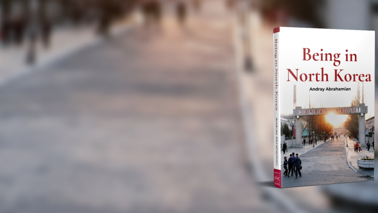 Cover of the book Being in North Korea on the background of a road with blurred figures walking