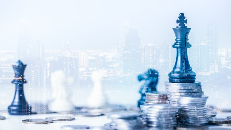Double exposure image of the coin stack which has the Staunton chess set such as king on top and overlay with cityscape image. The concept of economy, investment, and competition.