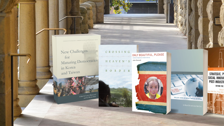 Covers of Korea Program books on the backdrop of Encina Hall colonnade, Stanford