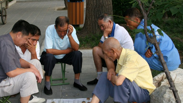 A group of Chinese elderly men sitting outdoors, playing a board game.